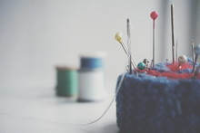 Close-up Of Sewing Needle And Thumbtacks On Pin Cushion Over White Background