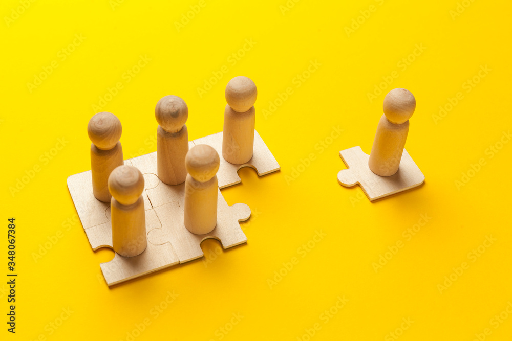 Fototapeta Wooden figures on puzzles on yellow background as a symbol of team building. Organization group people in business. Cooperation and partnership.