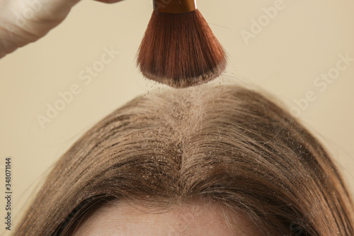 Tablou Canvas Close up view at woman applaying natural dry shampoo on hair roots