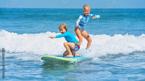 Tablou Canvas Happy baby boy and girl - young surfers ride with fun on one surfboard