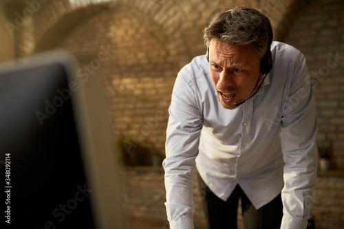 Displeased businessman shouting during video call at the office. Canvas Print