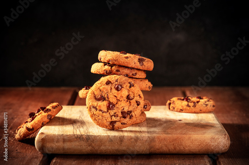 Fotografia Chocolate chip cookies stack on a dark rustic wooden background