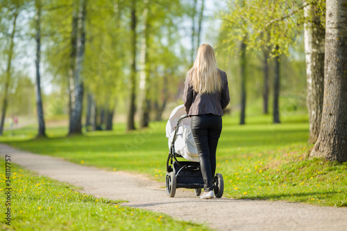 Vászonkép One young mother pushing white baby stroller and slowly walking at town green park in warm, sunny spring day