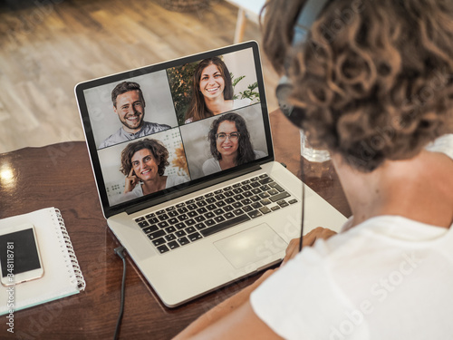 Photo woman having a video conference call with four people at her laptop wearing a he