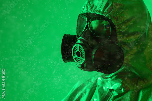 Photo Portrait of a man in profile in a radiation suit and gas mask on a green background
