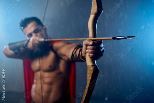 Muscular mature spartan shooting from bow. Fototapeta
