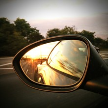 Car Reflecting On Rear-view Mirror Against Sky