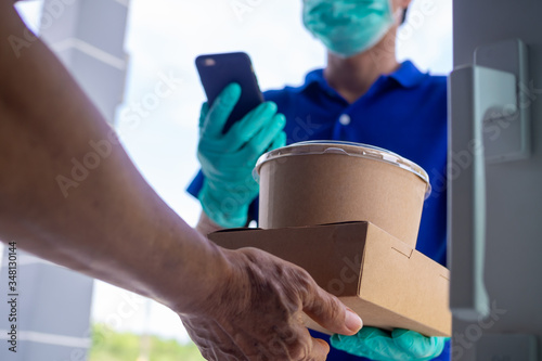 Valokuva Online orderers accepting food boxes from deliveryman wearing blue uniform with masks and gloves