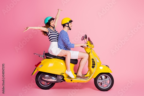Fototapeta Profile side view portrait of his he her she nice attractive lovely cheerful cheery glad couple riding moped having fun fooling celebrating isolated on pink pastel color background obraz