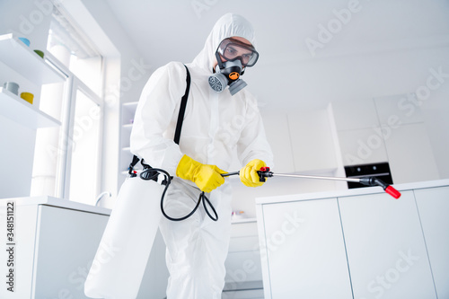 Fototapeta Low angle view photo of focused guy worker hold sprayer latex gloves gas glasses hands spray steam decontaminate ncov epidemic spreading in house kitchen indoors obraz