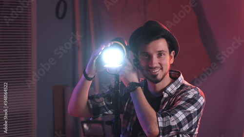 Fototapeta Close-up shot of Male filmmaker adjusting professional light stand in studioand smiling to the camera