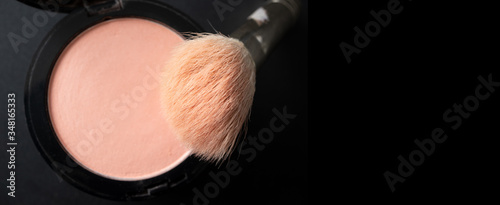Vászonkép Makeup brush and peach blush with selective focus on black background horizontal banner format with copy space, top view