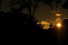Sun Peeking Through Silhouetted Trees At Sunset