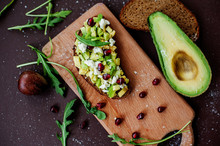 Sliced Fresh Avocado Fruit And Sandwich With Avocado, Cottage Cheese And Pomegranate Seeds On Cutting Board On Table Close Up. Healthy Food Concept. Selective Focus.