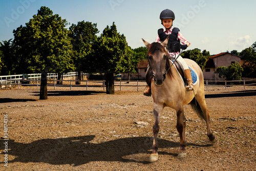 Fototapeta Girl riding her horse on farm paddock. Young jockey equestrian girl riding a brown horse in the summer. obraz