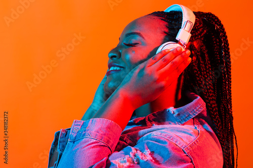 Photo Neon portrait of young african woman listening music with earphones