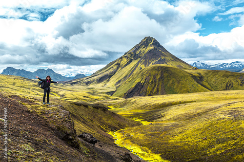 A young woman on a green mountain and a beautiful river of moss on the 54 km tre Canvas Print
