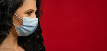 Girl With Dark Hair In A Medical Mask On Her Face Against A Red Wall.