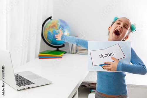 Little girl at speech therapist office, little girl learns vocal on laptop onlin Canvas-taulu