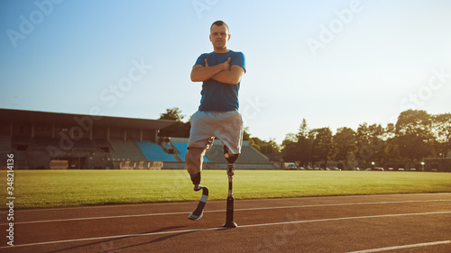 Athletic Disabled Fit Man with Prosthetic Running Blades is Posing with Crossed Arms on an Outdoor Stadium on a Sunny Afternoon Fototapet