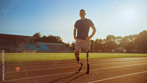 Fotografie, Tablou Athletic Disabled Fit Man with Prosthetic Running Blades is Posing During a Training on an Outdoor Stadium on a Sunny Afternoon