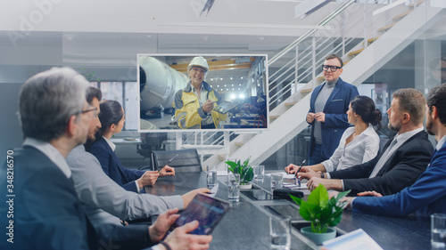 Fototapeta In the Conference Room Group of Directors, Investors and Businessmen Making Video Conference Call To Talk with Professional Female Engineer working in Industrial Factory obraz