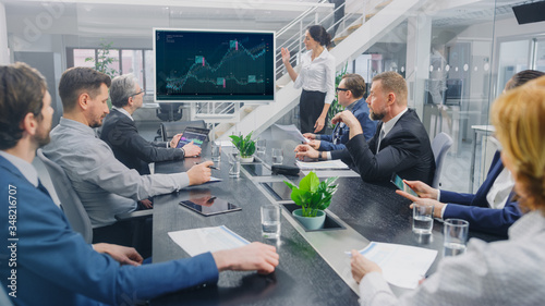 Photo In the Corporate Meeting Room: Female Analyst Uses Digital Interactive Whiteboard for Presentation to a Board of Executives, Lawyers, Investors
