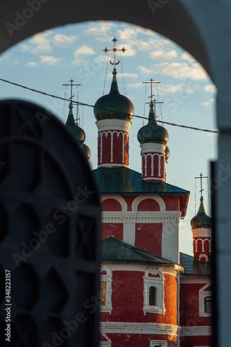 through an ajar gate opens a view of a beautiful red church Wallpaper Mural