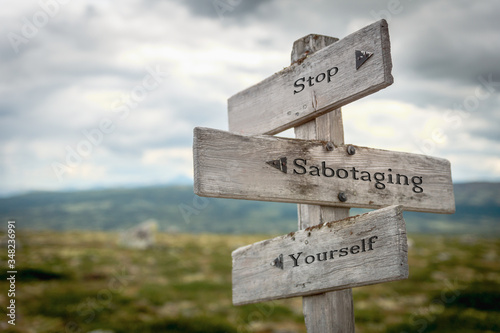 Fotografie, Tablou stop sabotaging yourself text engraved on old wooden signpost outdoors in nature