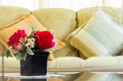 Beautiful artificial flowers in vase on mirror table with sofa and backrest pillow background in living room Canvas Print