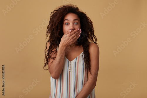 Photo Bemused young pretty dark skinned brunette female with long curly loose hair cov
