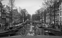 Bicycles Parked On Bridge Over Canal