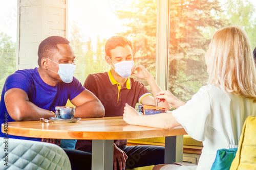 multinational group of happy friends in medical mask enjoy and drinking tea cafe Canvas Print