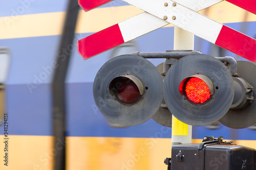 Red stop signal at a level crossing with a train in the background Canvas-taulu