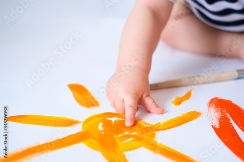 Fotografering Cropped baby crawls on the floor playing with paint, showing finger yellow painted sun close up