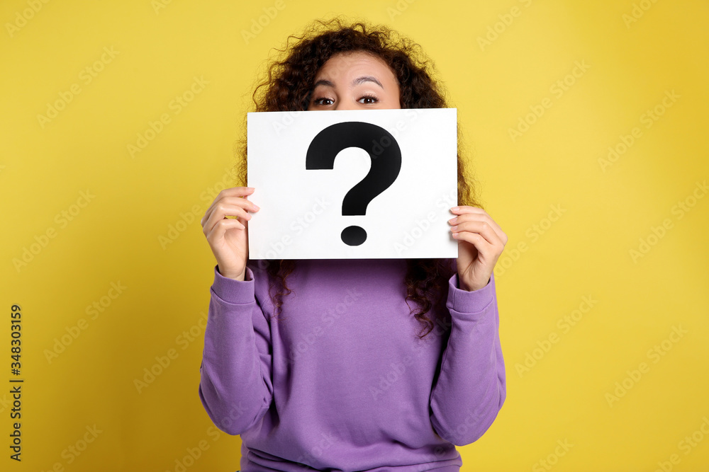 Fototapeta African-American woman with question mark sign on yellow background