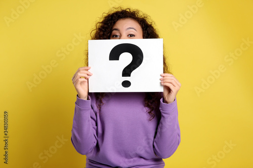 Fototapeta African-American woman with question mark sign on yellow background obraz