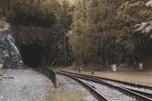 Train Tracks Leading To Tunnel