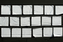 Square Sheets Of Paper Glued On A Black Wooden Board.