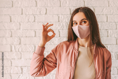 Cuadros en Lienzo Portrait happy woman in stylish medical face mask showing okay gesture with hand