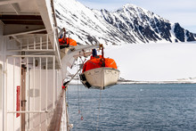 Lowering Orange Lifeboat To Water In Arctic Waters, Svalbard. Abandon Ship Drill. Lifeboat Training. Man Over Board Drill.