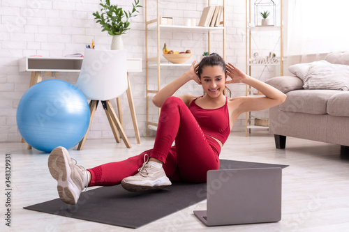Photo Latin girl exercising to live bodyweight workout on laptop, doing abs exercise a