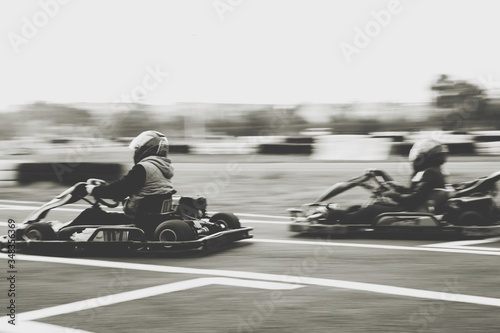 Cuadros en Lienzo Blurred Motion Of Men Racing In Go-carts Track