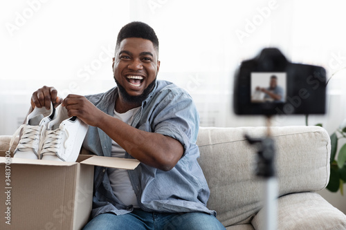 Vászonkép Joyful Black Man Blogger Recording Unboxing Video Of New Pair Of Shoes