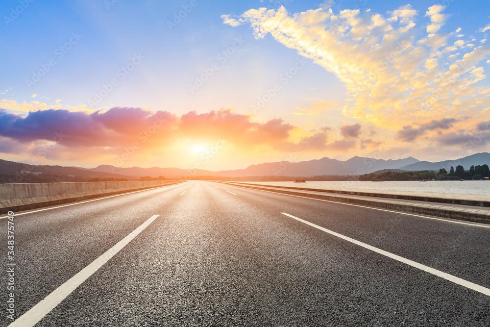 Fototapeta Asphalt road ground and mountain landscape at sunset.