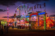 Illuminated Ferris Wheel At Amusement Park Against Sky