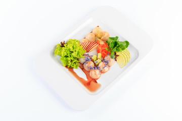 Sushi, danie kuchni japońskiej, podane na białym talerzu, dodatki warzywa i sałaty.