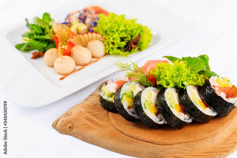 Obraz Rolki sushi na drewnianym talerzu w kształcie ryby. fototapeta, plakat