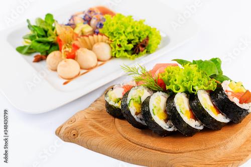 Fototapeta Rolki sushi na drewnianym talerzu w kształcie ryby. obraz