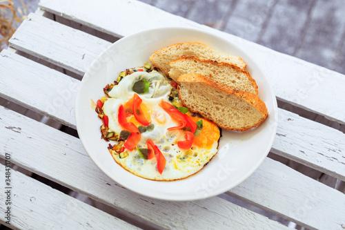 Fototapeta Smażone jajka, omlet, potrawa na śniadanie, biały talerz, dodatki sałatka i warzywa oraz pieczywo. obraz
